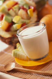 Glass of milk with sliced fruit on plate sitting next to a wooden spoon on place mat and fruit salad in the background, close-up, tilt, selective focus